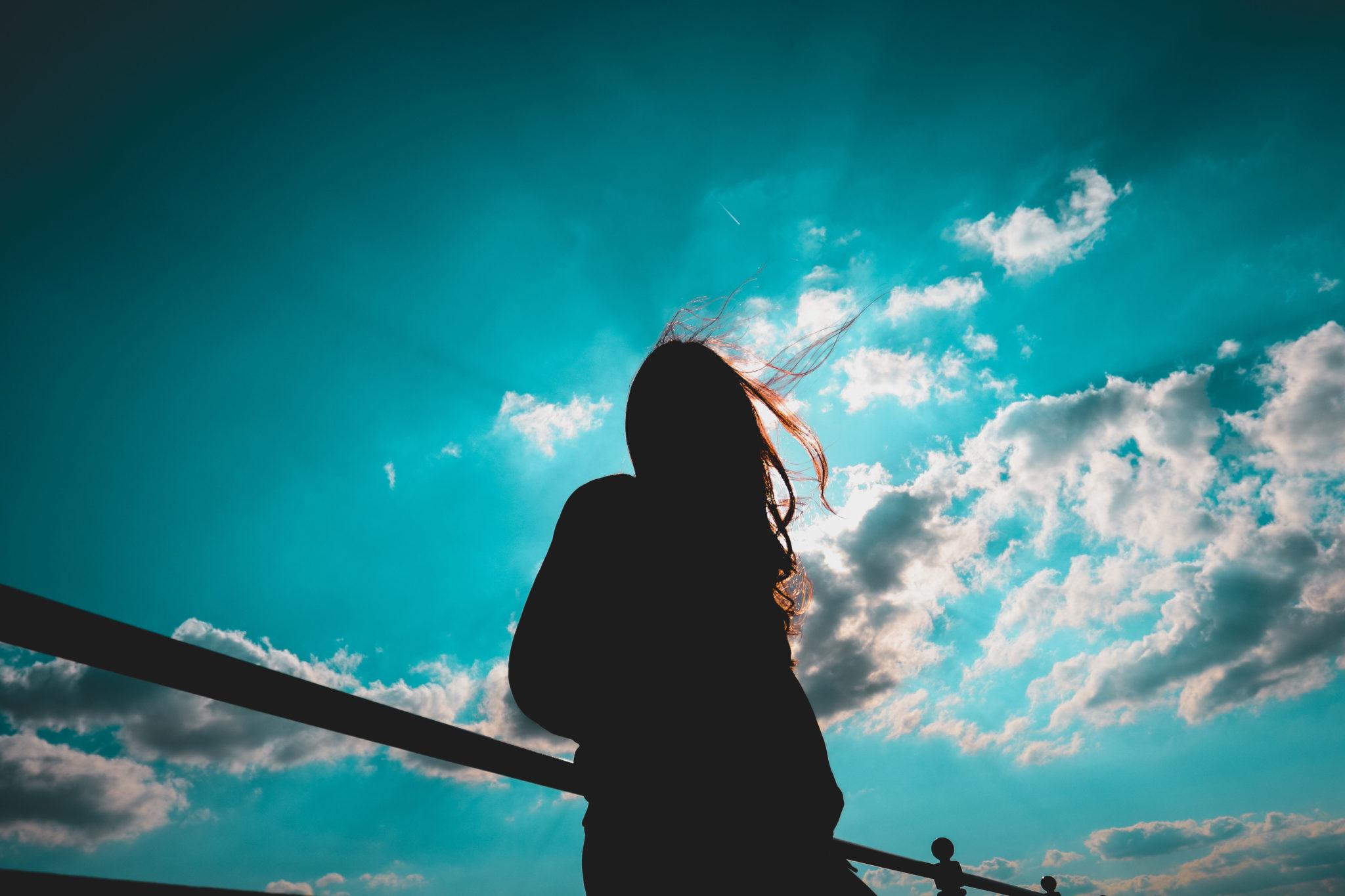 Tytön siluetti sinistä taivasta vasten.